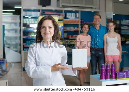 Woman pharmacist wearing white coat standing among shelves in pharmacy