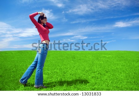 woman photographer in field under blue sky and clouds
