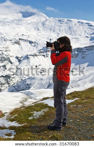 Woman photographer in Grossglockner, National Park Hohe Tauern, Austria - stock photo