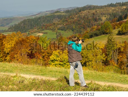 Woman  photographer in the mountains in autumn  - stock photo