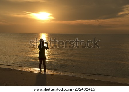 woman photographer silhouette by the shore at sunset - stock photo