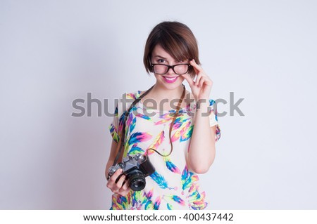 Woman photographer with camera against gray background - stock photo