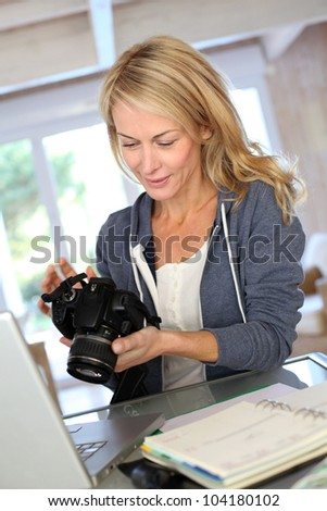Woman photographer working from home on laptop