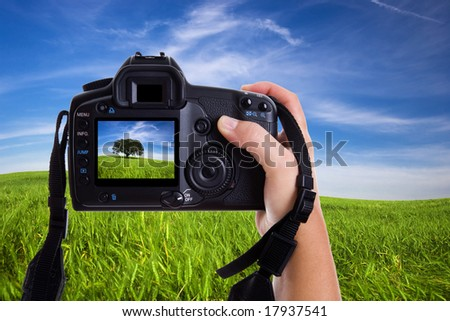 Woman photographing landscape with digital photo camera - stock photo