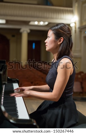 Woman pianist sits at the piano in empty concert hall - stock photo