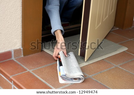 Woman picking up morning paper through the open door - stock photo