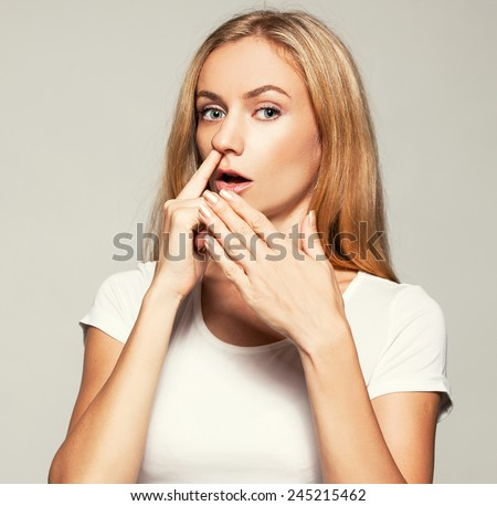 Woman picks his nose finger. Female climbs a finger in nose. Embarrassment - stock photo