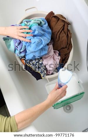 woman Pile of dirty laundry in bath washing machine green bathroom - stock photo