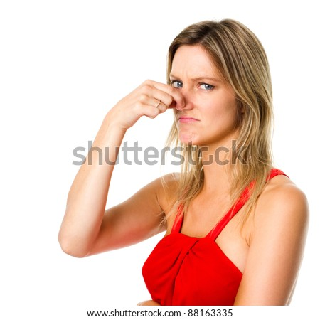 Woman pinches her nose to block a bad smell - stock photo
