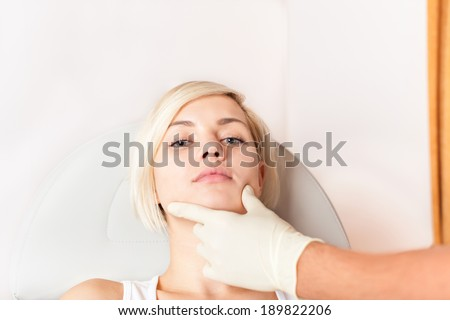 woman plastic surgery clinic, doctor hand in glove hold examine female face. cosmetic hospital medical beauty - stock photo