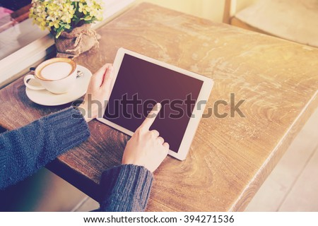 woman play tablet computer in coffee shop with vintage tone. - stock photo