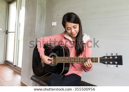 Woman play with guitar at home