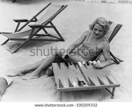 Woman playing backgammon on beach - stock photo