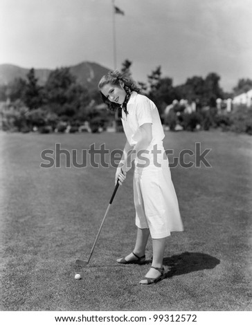 Woman playing golf on a golf course - stock photo