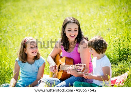 Woman playing guitar to her children in nature on sunny summer day