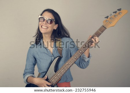 Woman playing music on a bass guitar - stock photo