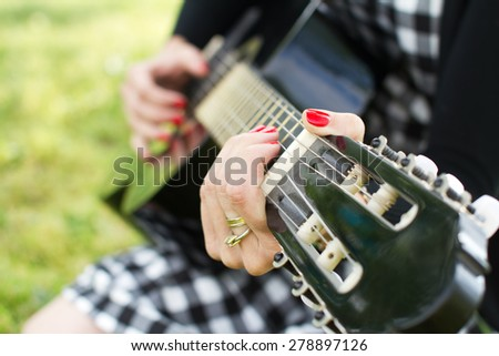 Woman playing on guitar detail - stock photo