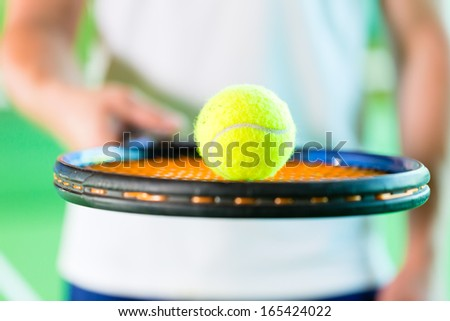 Woman playing tennis, only upper body with racket and ball, giving service - stock photo