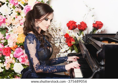 Woman playing the piano on flower background - stock photo