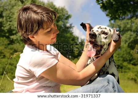 woman playing with a dog outdoors - stock photo