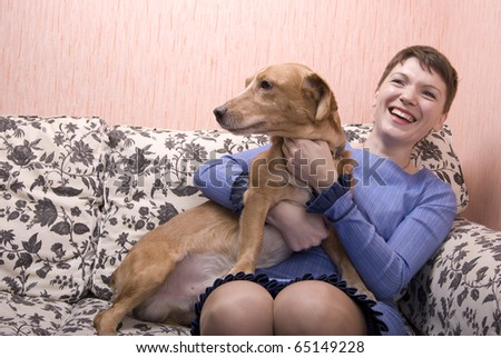 Woman playing with her cat in her apartment - stock photo