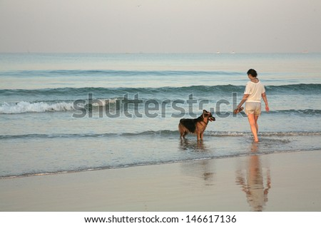Woman playing with her dog, India beach