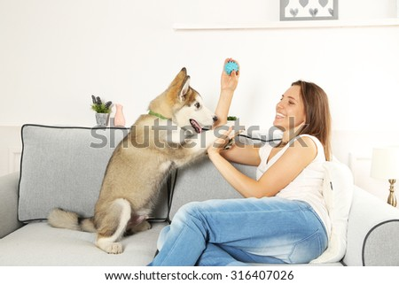 Woman playing with malamute dog on sofa in room - stock photo