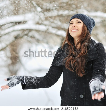Woman playing with snow in a winter park  - stock photo