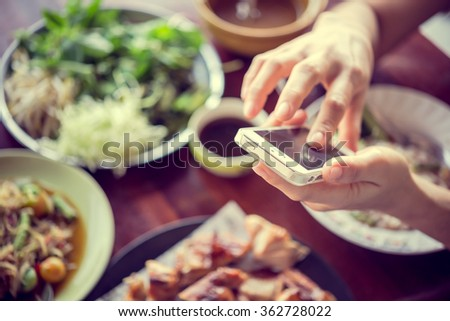 Woman playing with the phone in a restaurant with ambient light. Play on Phone,select focus - stock photo