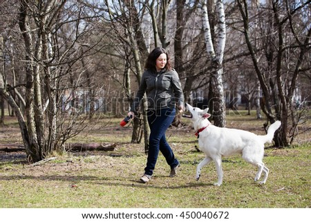 Woman playing with white swiss shepherd dog