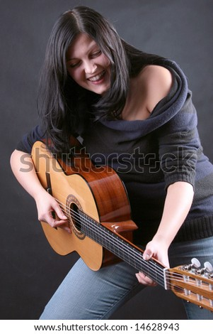 Woman plays on the classic guitar - stock photo