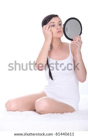 Woman plucking eyebrows - stock photo