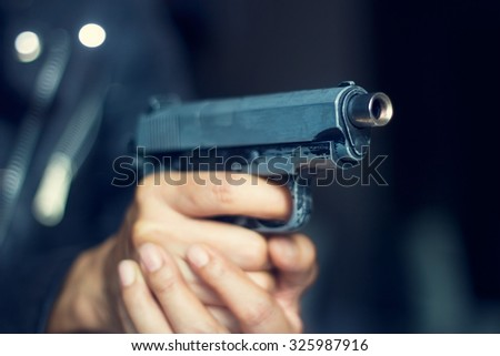 Woman pointing a gun at the target on dark background, selective focus on front gun - stock photo