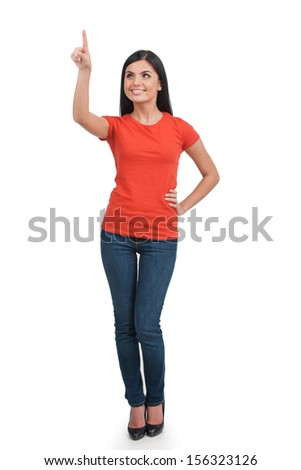 Woman pointing. Full length of cheerful young woman pointing away and smiling while standing isolated on white - stock photo