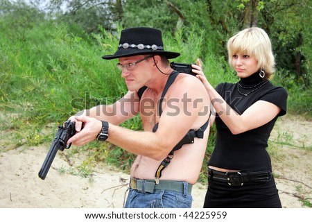 woman pointing gun at surrendering man with revolver wearing cowboy hat, sand and trees on background - stock photo