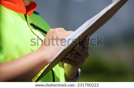 Woman police officer fills out the form for car driver - stock photo