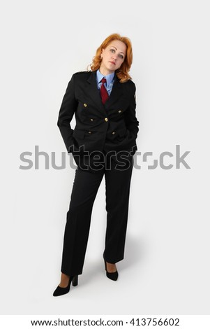 Woman police officer in uniform stands full height on gray background - stock photo