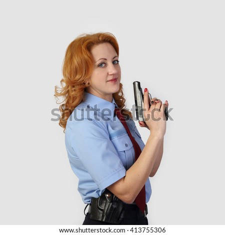 Woman police officer with handgun on gray background in square - stock photo