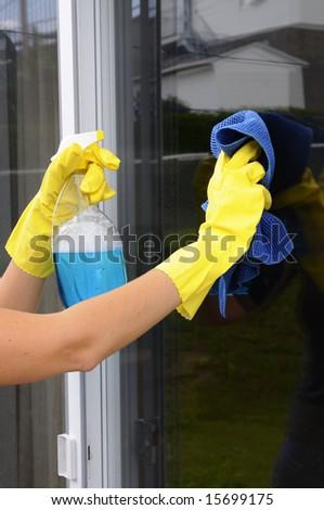 woman polishing glass door using microfiber cloth and yellow latex gloves - stock photo