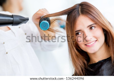 Woman portrait blow drying her hair at the beauty salon - stock photo