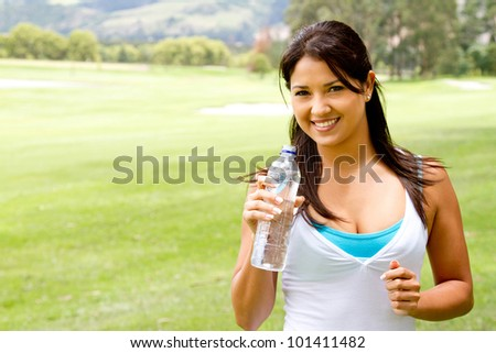 Woman portrait drinking water after exercising outdoors - stock photo