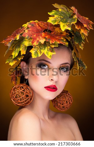 Woman portrait in autumn fashion concept. Art style. Season. Gold leaves. Model. Beauty and fashion - stock photo