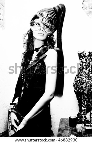 woman portrait in black and white wearing mask - stock photo