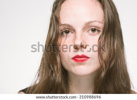 Woman portrait in stripes dress with red lips  freckles studio - stock photo