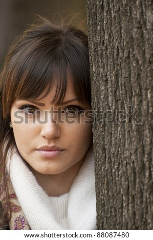 Woman portrait outdoors leaning on a tree - stock photo