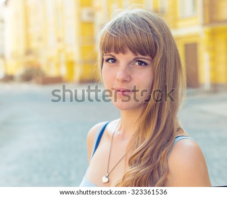 Woman portrait. Portrait of pretty young woman, close up. Beautiful girl on the background town houses. She is on the walk. - stock photo
