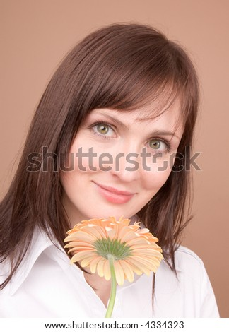 Woman portrait with flower isolated on beige background - stock photo