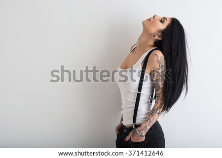Woman portrait with tattoo against white wall background.