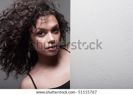 Woman posing from behind a wall