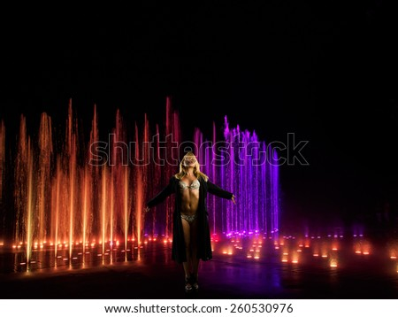 Woman posing in front of light and water show - stock photo